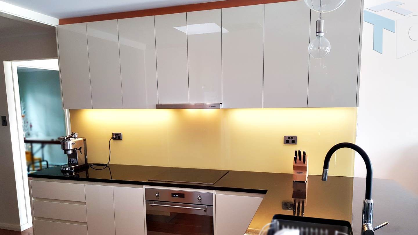 kitchen-angle-view-oven-cooktop-yellow-splashback-sink